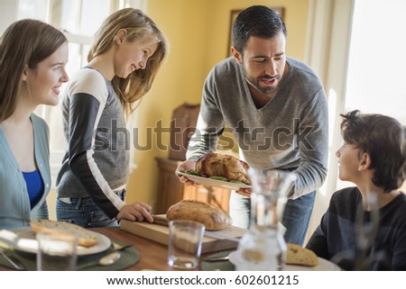 Adults and children gathered around a table for a meal #602601215