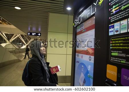 KUALA LUMPUR, MALAYSIA - 1ST MARCH 2017. A young woman trying to use the vending machine Shop & Fly at Kuala Lumpur Internation Airport. #602602100