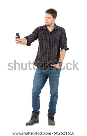 Young casual handsome man taking low angle selfie with smart phone.  Full body length portrait over white studio background. #602621618