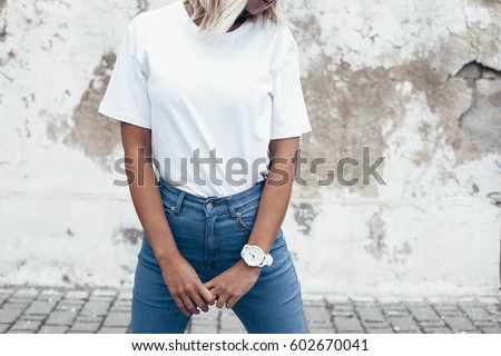 Hipster girl wearing blank white t-shirt and jeans posing against rough street wall, minimalist urban clothing style, mockup for tshirt print store Royalty-Free Stock Photo #602670041