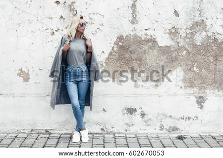 Hipster girl wearing blank gray t-shirt, jeans and coat posing against rough street wall, minimalist urban clothing style, mockup for tshirt print store #602670053