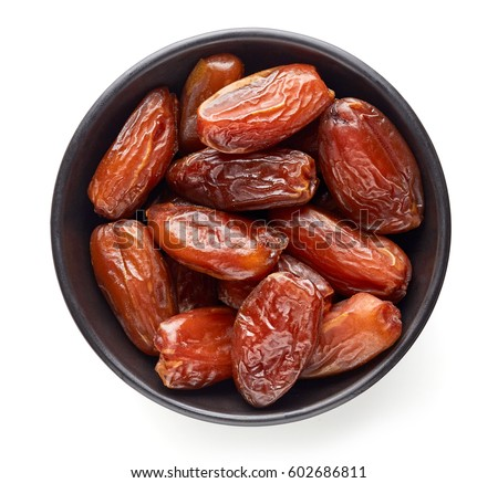 Bowl of pitted dates isolated on white background, top view Royalty-Free Stock Photo #602686811