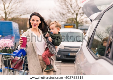 Woman with little son near car after shopping in grocery shopping #602753318