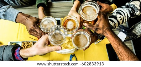 Top view of friends cheering with home brew in pub bar restaurant - Young people hands toasting and beers half pint - Party concept - Warm filter - Focus on bottom hands glasses Royalty-Free Stock Photo #602833913