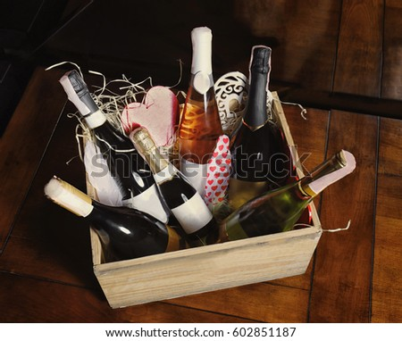 Wooden crate with wine bottles on table #602851187