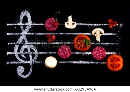 Concept of cooking pizza, like notes from ingredients. Salami, tomato and mozzarella cheese on a black background with a treble clef. #602954984