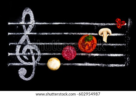 Concept of cooking pizza, like notes from ingredients. Salami, tomato and mozzarella cheese on a black background with a treble clef #602954987