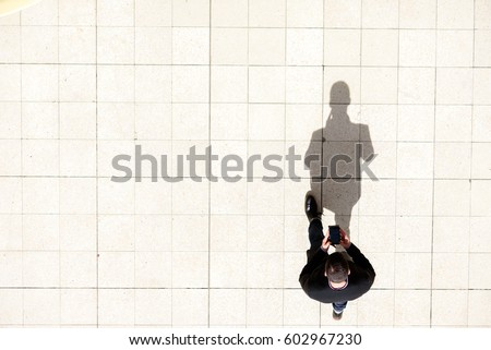 Man walking and texting on his mobile phone shot from above