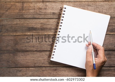 hand  writing on notebook with wood pencil #602973302