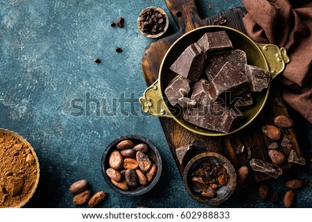 Dark chocolate pieces crushed and cocoa beans, culinary background, top view #602988833