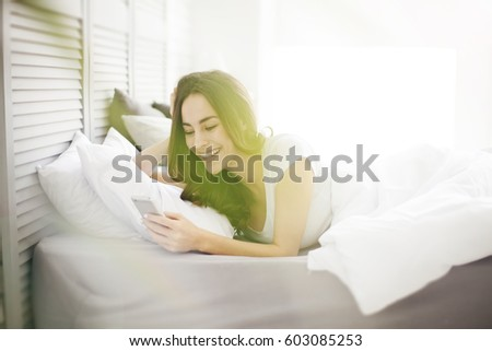 Happy brunette girl using a mobile phone lying on the white bed at home with a window in the background. #603085253