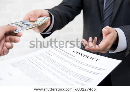 Businessman giving money together with contract - debt, loan and bribery concepts #603227465