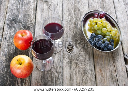 glasses of wine and apples, grapes on old wooden table #603259235