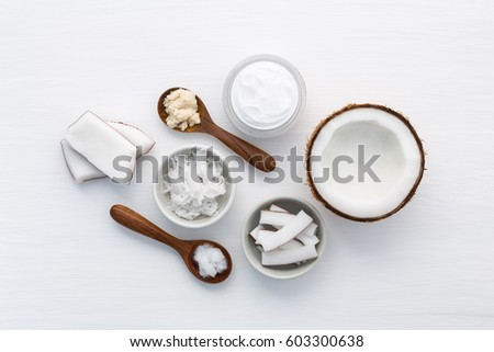 Homemade coconut products on white wooden table background. Oil, scrub, milk and lotion from top view. Good for space and background. #603300638