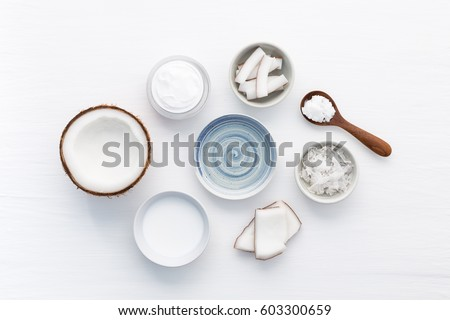 Homemade coconut products on white wooden table background. Oil, scrub, milk and lotion from top view. Good for space and background. #603300659