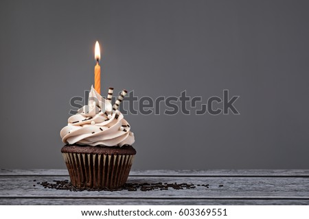 Chocolate Birthday cupcake with  buttercream icing and orange candle over a grey background. #603369551