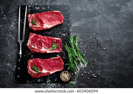 Raw meat, beef steak on black background, top view Royalty-Free Stock Photo #603406094