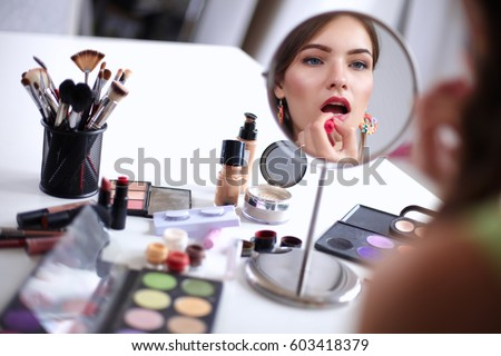 Young beautiful woman making make-up near mirror,sitting at the desk #603418379