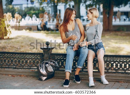 two  beautiful girls in stylish clothes in summer city #603572366
