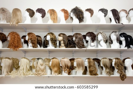 Row of Mannequin Heads with Wigs on the Shelf Royalty-Free Stock Photo #603585299