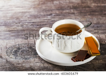 White Cup of tea. The tea party. Chocolate on the saucer. Selective focus. Wooden background #603601679