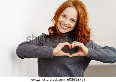 Pretty romantic young redhead woman making a heart gesture with her fingers in front of her chest showing her love and affection with a happy tender smile #603632939
