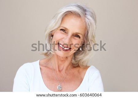 Close up portrait of beautiful older woman smiling and standing by wall #603640064