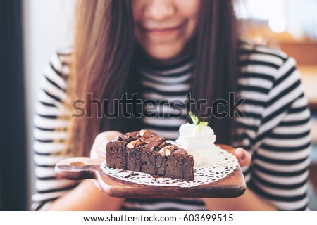 A beautiful asian woman holding brownie cake and whipped cream with feeling happy and good lifestyle in the modern cafe #603699515