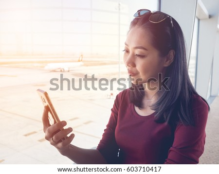 Asian woman use smartphone in the airport with morning sunlight. #603710417