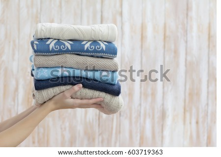 Stack of warm blue sweaters, woman holding in hands