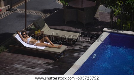 The territory of the hotel. The girl in a white bathing suit lying on a lounger by the pool. It relaxes and gets pleasure from their holidays.  #603723752