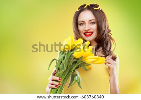 Beautiful young brunette woman with yellow tulips on green background #603760340