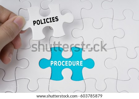 Hand holding piece of jigsaw puzzle with words Policies And Procedure. Royalty-Free Stock Photo #603785879