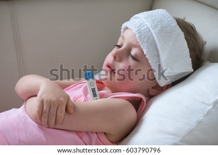 Sick child with high fever laying in bed and  holding thermometer.  Compress on forehead. Royalty-Free Stock Photo #603790796