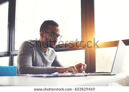 Concentrated afro american copywriter in glasses working on text editing creating advertising campaign for website sitting in coffee shop using modern laptop computer connected to wireless internet