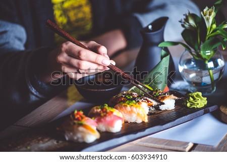 Man eating sushi set with chopsticks on restaurant #603934910