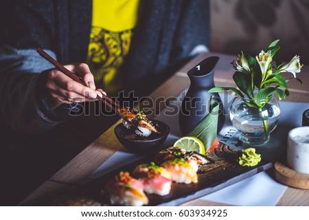 Man eating sushi set with chopsticks on restaurant #603934925