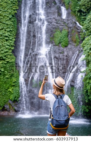 Travel and technology. Young woman in hat with rucksack taking photo of big waterfall on her smartphone.
