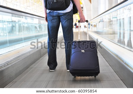 Traveler with a bag on the speedwalk #60395854