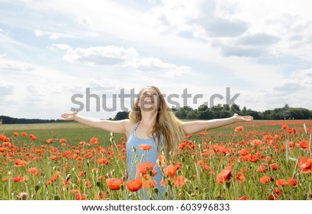 happy young blond woman cheering in poppy field #603996833