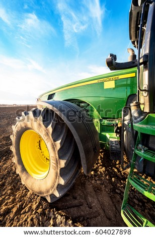 Varna, Bulgaria - March 5, 2017 Ploughing a field with John Deere tractor. John Deere was manufactured in 1995-1999 and it has JD 7.6L or 8.1L 6-cyl diesel engine. #604027898