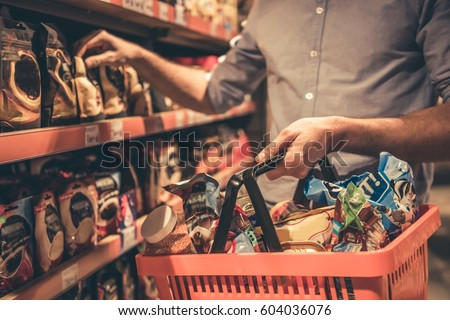 Cropped image of handsome man with a market basket doing shopping at the supermarket Royalty-Free Stock Photo #604036076