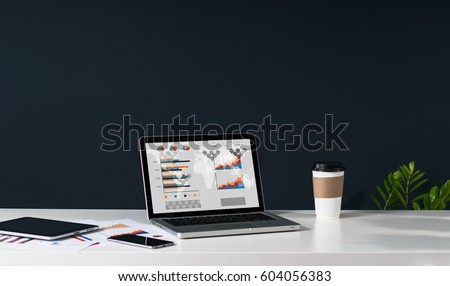 Close-up of laptop with graphs, charts and diagrams on screen on white table. Nearby is tablet computer, smartphone, paper graphics, cup of coffee. In background dark wall. Empty workplace. #604056383