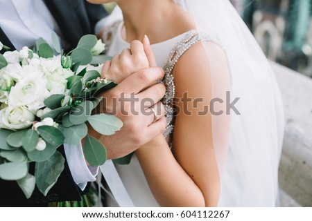 Close-up of groom's hand holding bride's wirst tender Royalty-Free Stock Photo #604112267