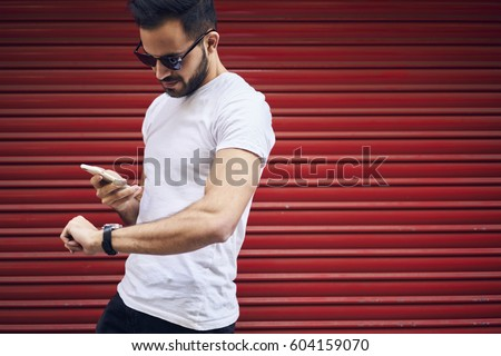 Handsome young bearded man in eyewear and casual outfit receiving text mail with invitation for meeting in cafe strolling outdoors hurrying to get there in time passing copy space for advertising #604159070
