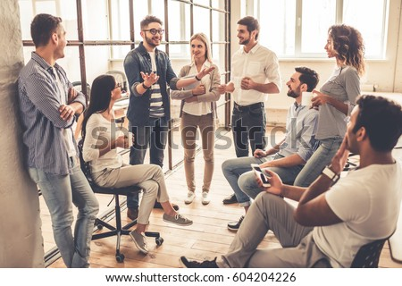 Successful young business people are talking and smiling during the coffee break in office Royalty-Free Stock Photo #604204226
