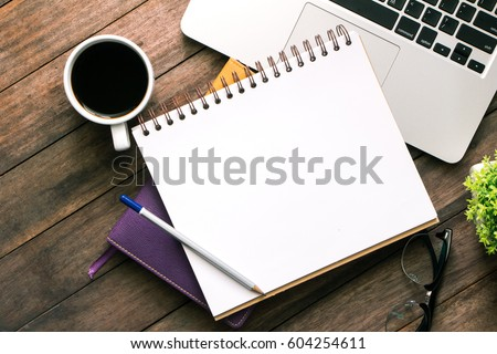 Office table with blank notebook and laptop / Coffee cup Royalty-Free Stock Photo #604254611