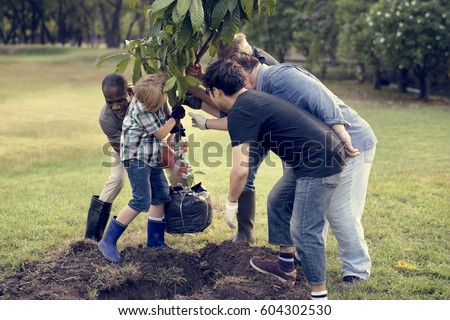 Group of Diverse People Planting Tree Together Royalty-Free Stock Photo #604302530