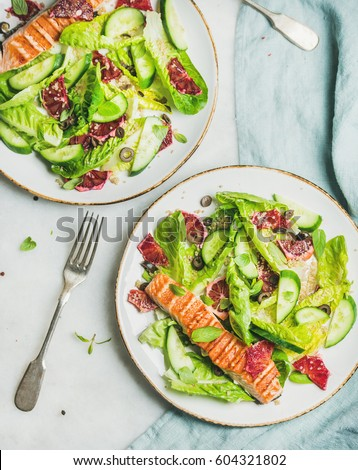 Healthy energy boosting spring salad with grilled salmon, blood orange, olives, cucumber and quinoa in white plates, top view, marble background. Clean eating, dieting, detox, weight loss concept #604321802