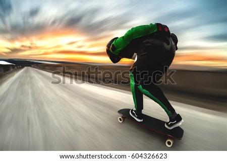 A man in a helmet and leather suit, in a rack at high speed, rides on a long longboard for downhill on afsalt against the backdrop of the setting sun in the light of the setting sun. Royalty-Free Stock Photo #604326623